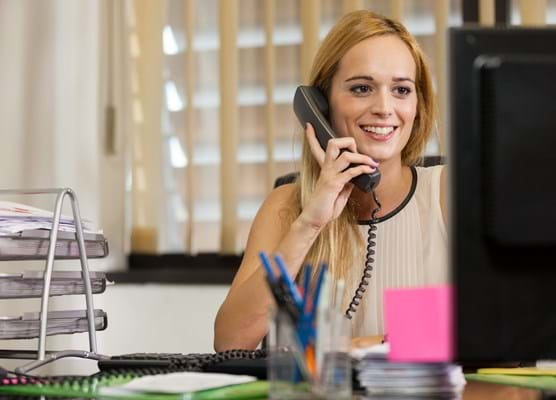 woman sat at her desk in an office on the telephone
