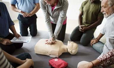 group of employees in an office learning CPR first aid training at the office