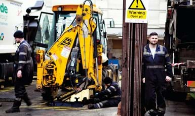 small yellow JCB in a garage with 2 male workmen