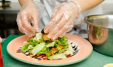 close up of person wearing plastic gloves plating up a salad on a plate